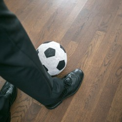 Person's foot with football ready for kicking