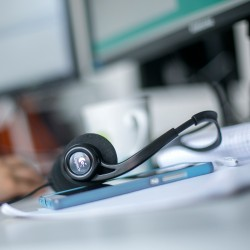 Headset on a desk near a computer keyboard